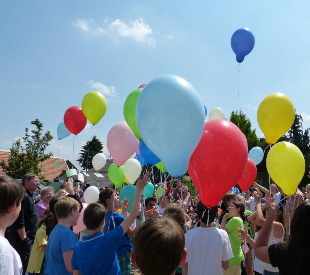 Die Schülerinnen und Schüler der Heinrich-Böll-Sekundarschule lassen Luftballons mit ihren Wünschen für die neue Schule aufsteigen.
