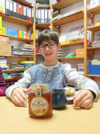 Ein Schüler sitzt glücklich vor seinem Frühstücksteller. Im Vordergrund, der von ihm mitgebrachte fair gehandelte Honig.